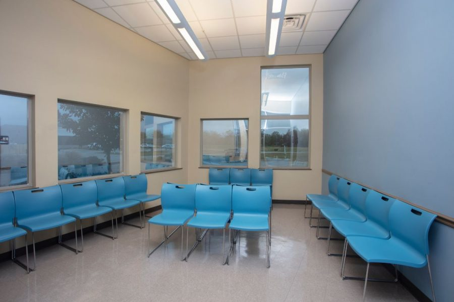Waiting room with bright blue chairs and view to the outside