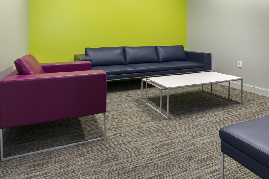 Small meeting room with couches and bright walls.