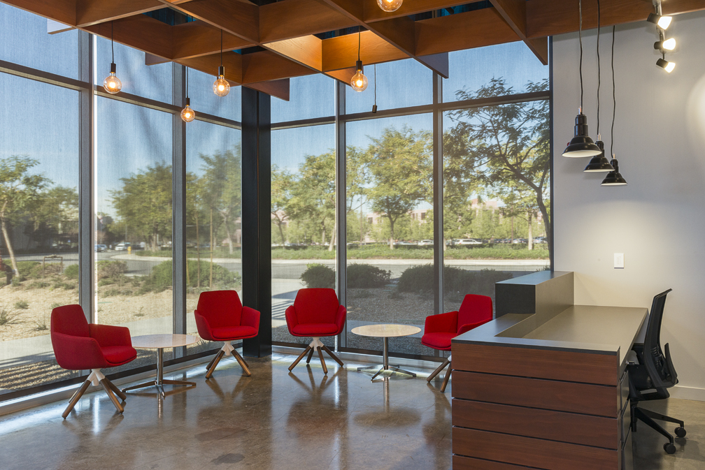 Reception area with large windows and bright red chairs.