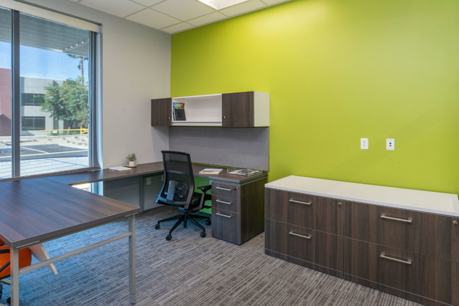 Private office with wood laminate surfaces with bright accent wall