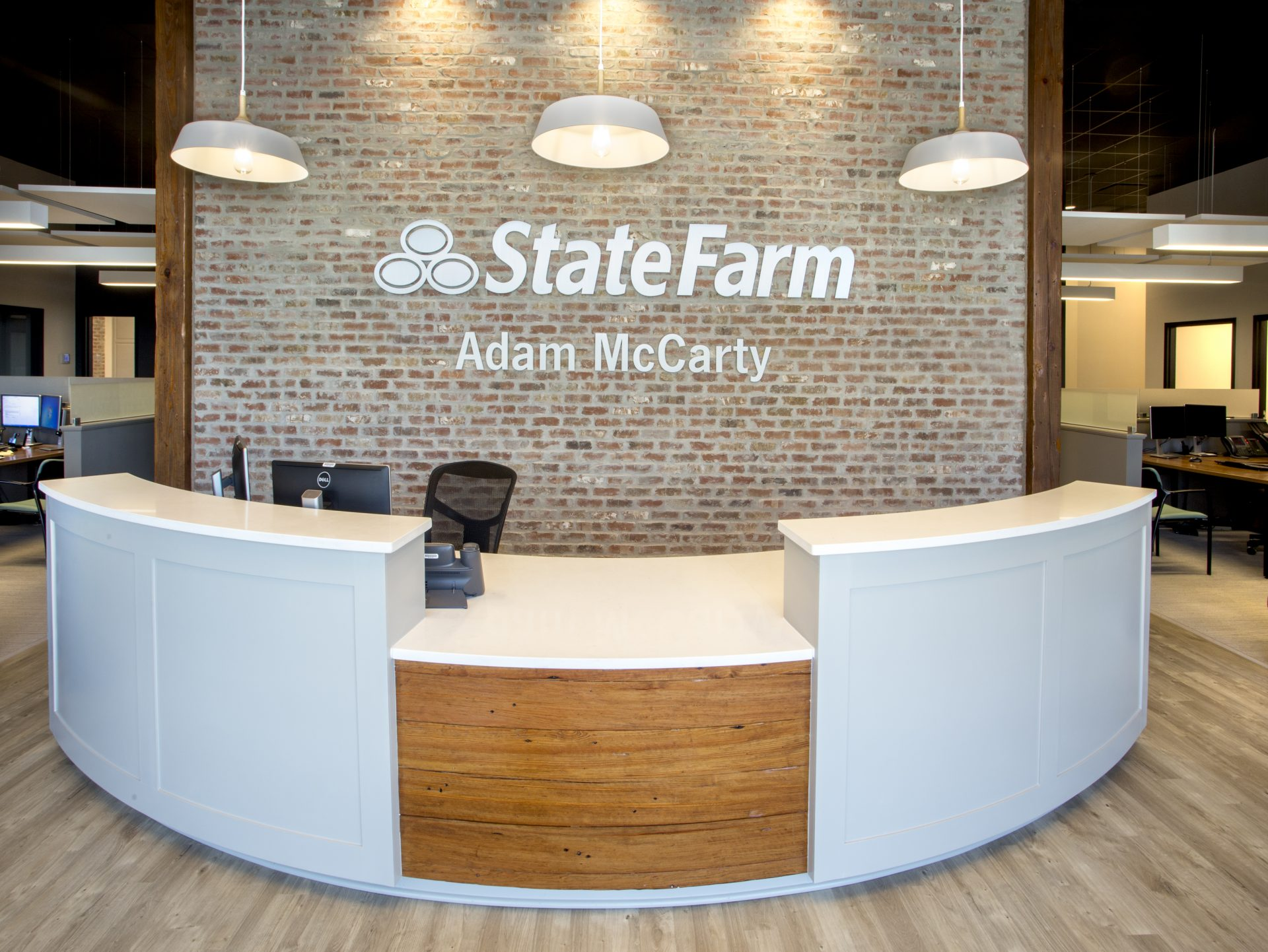 Adam McCarty State Farm front desk. Exposed brick and wood details.