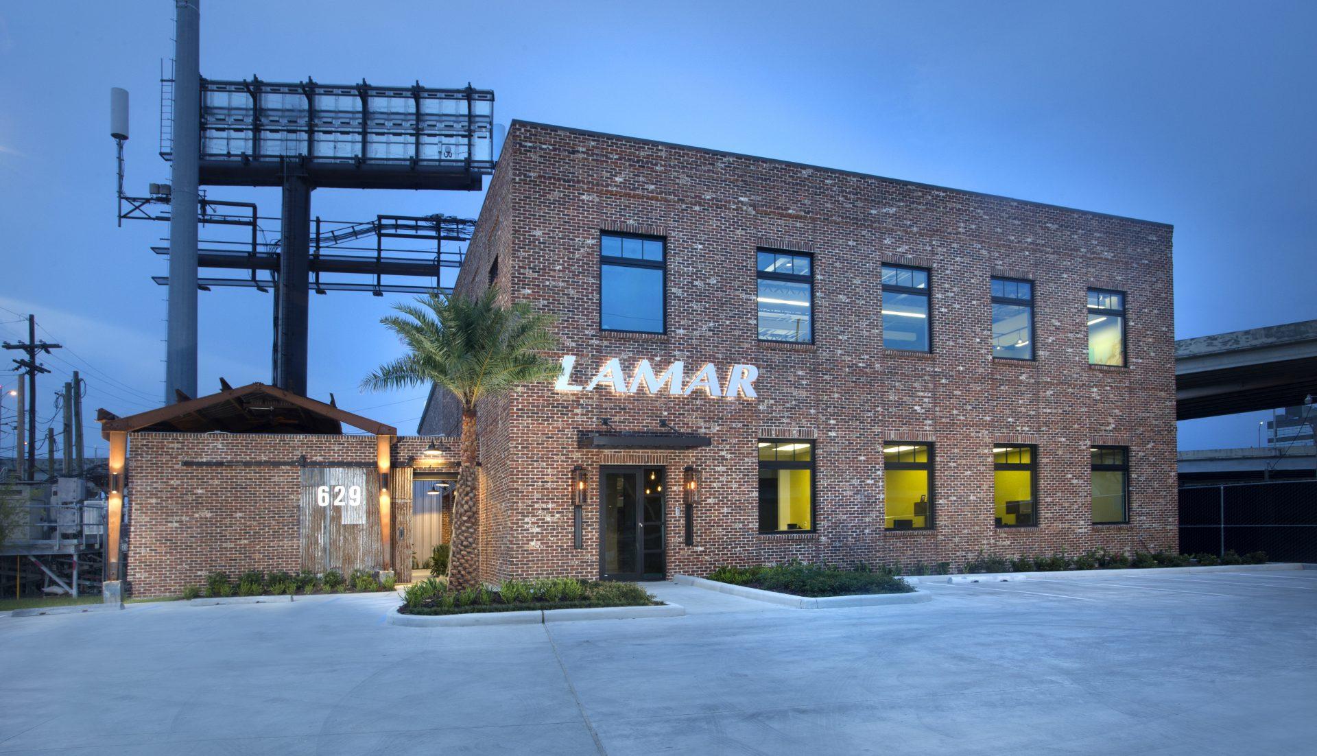 Lamar Advertising - New Orleans exterior at dusk with illuminated Lamar signage.