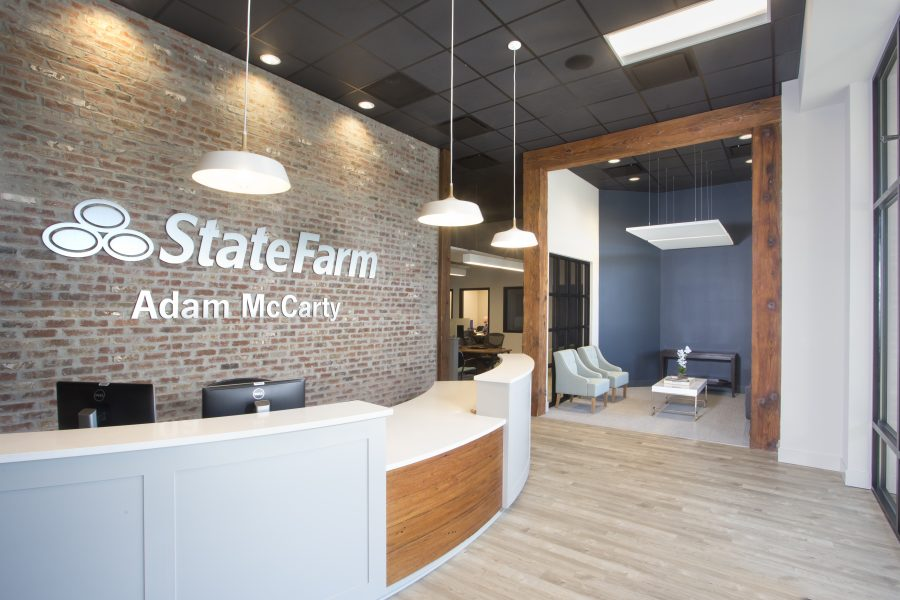 Adam McCarty front desk with exposed brick. Looks into the rest of the office with drop down lights and black ceilings.