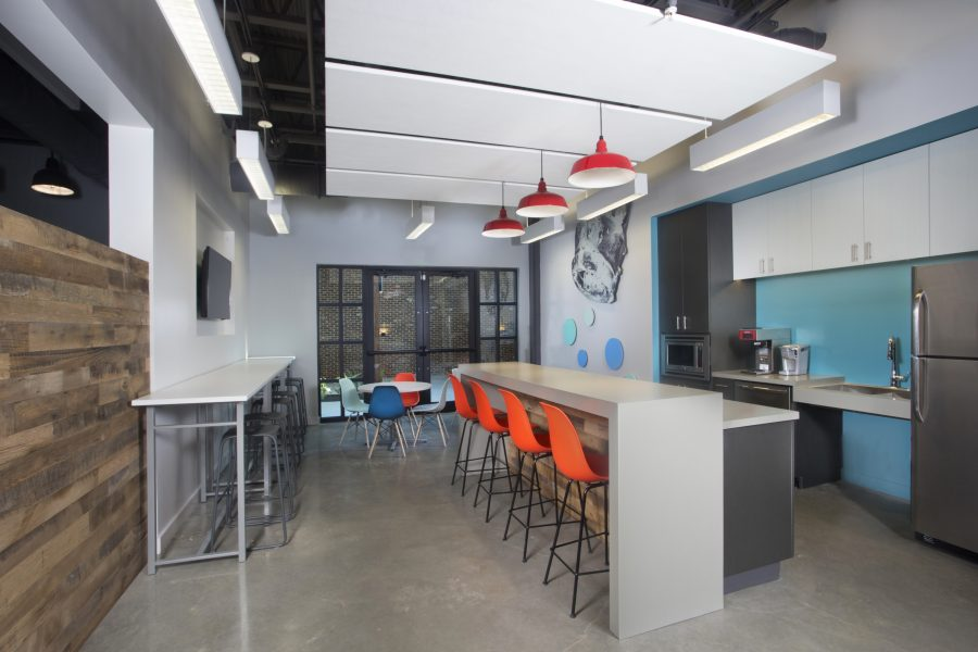 Bright break room with colorful chairs and red pendant lights
