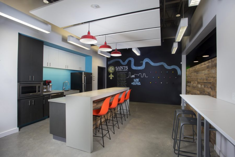 Bright break room with chalkboard wall and red pendant lights