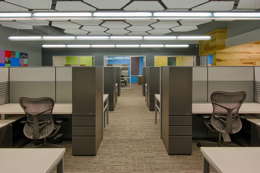 Open office space with desks and hexagon ceiling tiles.