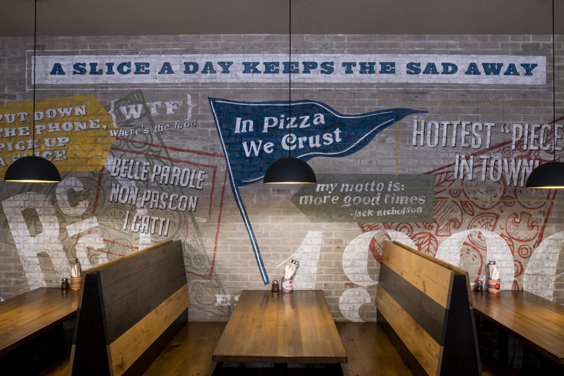 In Pizza We Trust painted on brick at booth seating