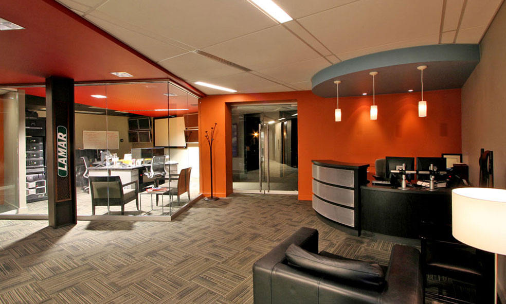 Orange accents at reception area with curved desk and glass walls