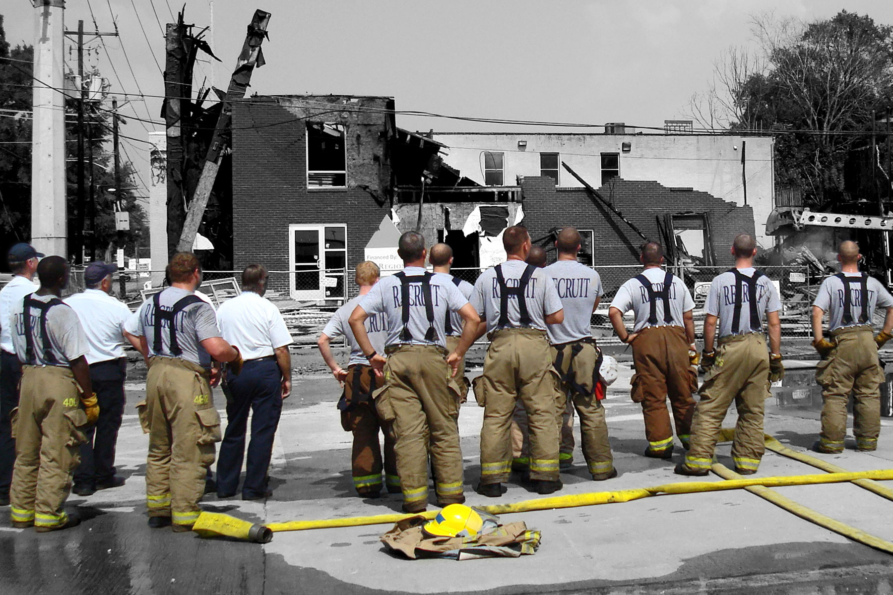Firefighters looking at a burned building
